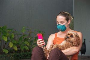 Masked holding Dog