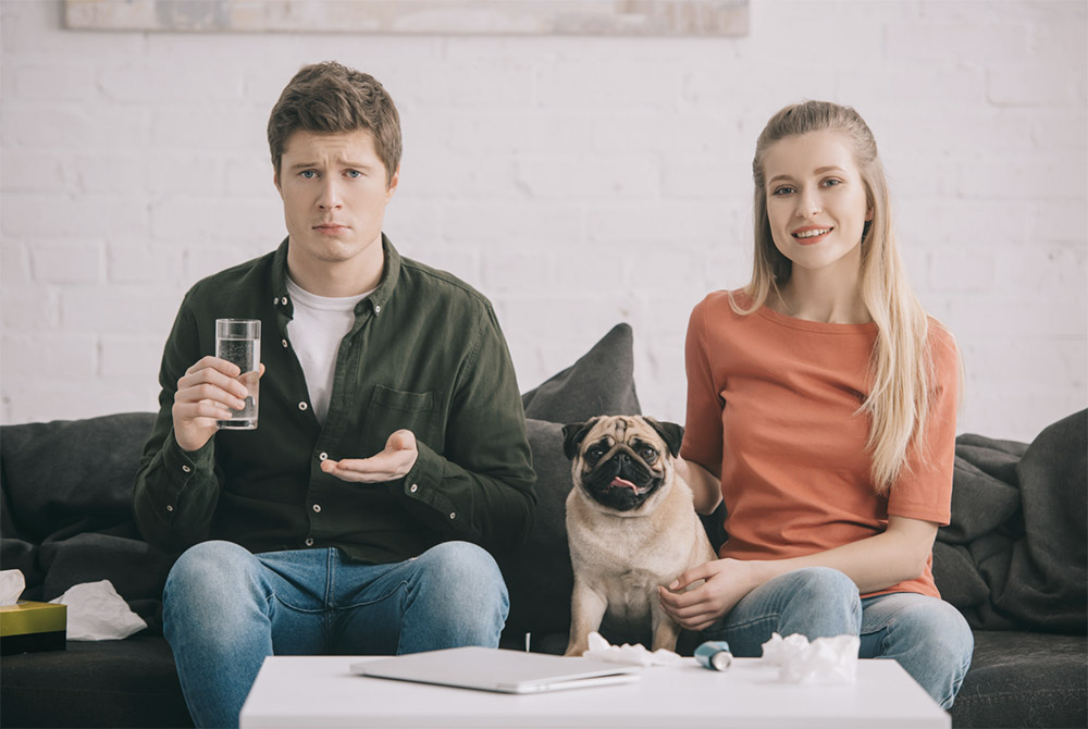 annoyed guy on couch next to dog