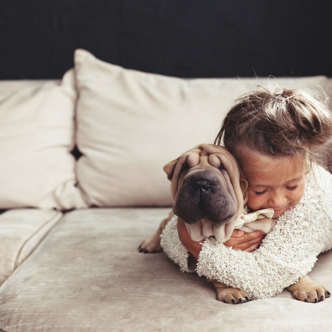 Child hugging her emotional support puppy